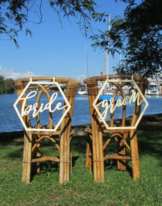 A wide angle image of the BRIDE and GROOM wooden chair signs. Both signs are placed on the back of matching wicker style chairs on the grass overlooking the river.