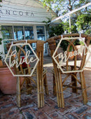 Load image into Gallery viewer, A wide angle mage of the BRIDE and GROOM wooden chair signs. Both signs are placed on the back of matching wicker style chairs in an outdoor reception setting.