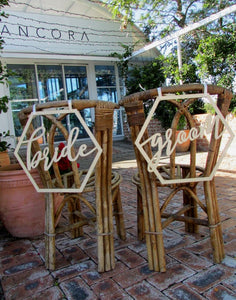 A wide angle mage of the BRIDE and GROOM wooden chair signs. Both signs are placed on the back of matching wicker style chairs in an outdoor reception setting.