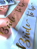 Load image into Gallery viewer, Bride to be hens party sashes in soft beach and a white option with gold writing and come in a gift box with ribbon