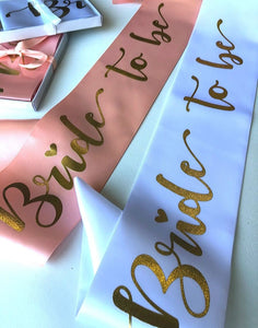 Bride to be hens party sashes in soft beach and a white option with gold writing and come in a gift box with ribbon