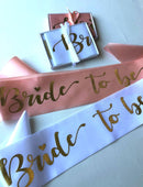 Load image into Gallery viewer, Bride to be hens party sashes in soft beach and a white option with gold writing laying flat with gift box and wrapped in a ribbon above it