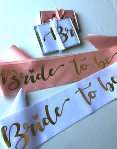 Bride to be hens party sashes in soft beach and a white option with gold writing laying flat with gift box and wrapped in a ribbon above it