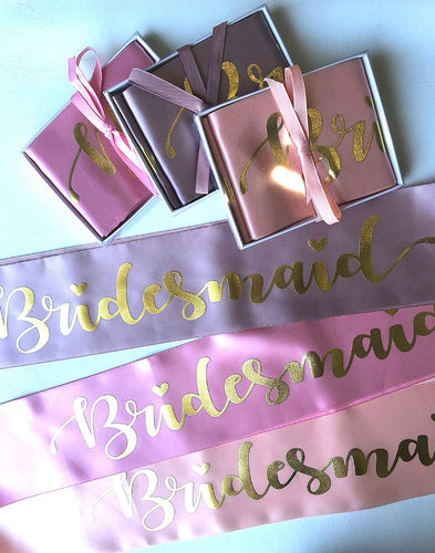 3 maid of bridesmaid sashes in white boxes with ribbon around it and 3 bridesmaid satin sashes laying flat in soft peach,