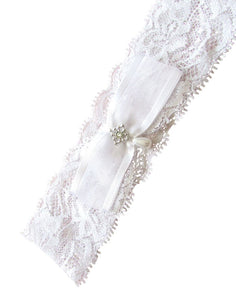 A wider angled image showing the Chenae Pearl Tear Drop Garter. With wide flower patterned soft stretch lace, organza ribbon bow, pearl teardrop and diamond shaped silver motif.