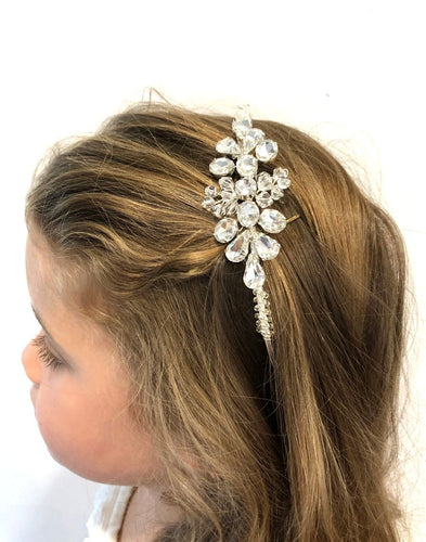 An image of the Cindy Bridal Headband showing it's placement on a blonde flowergirl's flowing hairstyle. The Headband is delicately handcrafted with glass Swarovski crystals on the centrepiece and the silver toned headband is twirled in glass crystals.