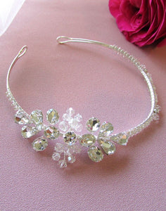An image of the Cindy Bridal Headband showing the delicately handcrafted piece with glass Swarovski crystals on the centrepiece and the silver toned headband is twirled in glass crystals.