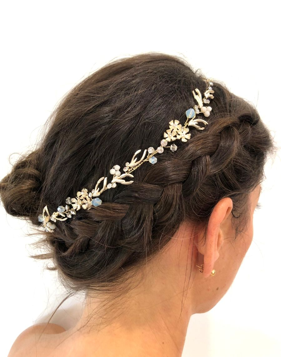An image of the Court Bridal Hair Vine with its floral and antler design of clear crystals, pearls and opalescent beads intricately placed on soft gold-toned moveable wiring. It is shown placed on a brunette up-do.