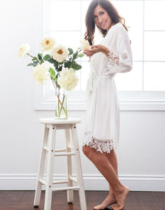 This image shows a brunette posed with cream coloured flowers, wearing the Dafne Robe in White Diamond. The luxe fabric drapes very flatteringly when fastened with the matching sash belt. The sleeve cuff and hem both are detailed with floral lace making this robe look ever so feminine and elegant.