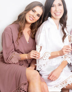 An image of a bride and a bridesmaid toasting a glass of bubbles. The brunette bridesmaid are wears the Dafne Robe in Rosewood Mauve and shows the flattering robe falling delicately with elegant lace detailing on the cuff's and hems.