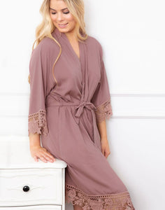 An image of a Blonde haired woman wearing the Dafne Robe in Rosewood Mauve. The image shows the luxe lace cotton fabric falling ever so flatteringly. The cuffs and hem have a beautiful lace detail and the robe is fastened with a matching sash belt.