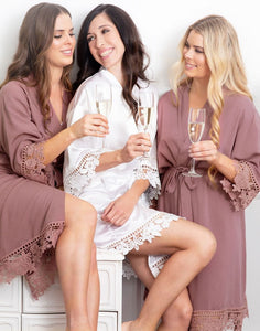 An image of a bride and two bridesmaids toasting a glass of bubbles. Both bridesmaids, one blonde and one brunette are wearing the Dafne Robe in Rosewood Mauve and show how this gorgeous robe suits all colourings. The robes fall delicately and are very flattering with elegant lace detailing on the cuff's and hems.
