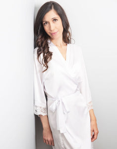 An image of the White Diamond Dorotea robe, which is being worn by a brunette lady. The delicate silk satin fabric drapes flatteringly when tied with the matching belt sash. The sleeves finished with a delicate matching lace, which makes this robe ever so elegant, and timeless.