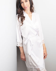 An image of the White Diamond Dorotea robe, which is being worn by a brunette lady. The delicate silk satin fabric drapes flatteringly when tied with the matching belt sash. The sleeves and hem are all finished with a delicate matching lace, which makes this robe ever so elegant, and timeless.