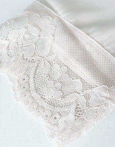 A closeup image of the elegant, delicate lace that details the sleeve cuff of this Dorotea Robe.