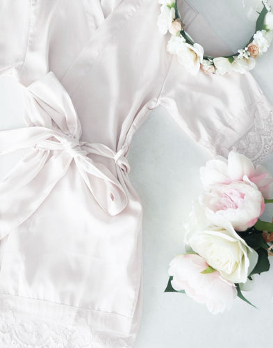 An Image of the Dorotea Flower Girl Robe. The white diamond robe is laid flay, showing its shape when fastened with the matching belt sash. The home and sleeve cuffs are detailed with elegant, delicate lace.