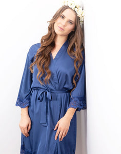 An image of a brunette lady wearing this beautiful blue sapphire Dorotea robe. The robe has a beautiful drape and is very flattering fastened with the matching belt sash around the waist. Delicate lace detailing is shown on the on the sleeve cuffs.