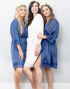 An image of a bride, and her two bridesmaids who are both wearing the Blue Sapphire Dorotea Robe. One a brunette, one a blonde showing how this beautiful sapphire hue compliments all colourings. The robes have a beautiful drape and are very flattering. There are matching belt sashes tied around the waists and delicate lace detailing on the sleeve and hem of the robes.