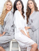 Load image into Gallery viewer, An image of a bride and her two bridesmaids, who are both wearing the Grey Moonstone Dorotea robe. One a brunette, one a blonde shows how this colour is flattering on all colourings. The robs are tied with a matching belt sash and the silky said fabric drapes very flatteringly to their knees. The robes have a delicate lace detail on the sleeves and hem.