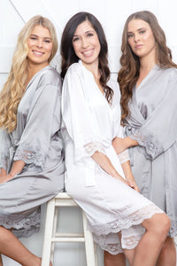 An image of a bride and her two bridesmaids, who are both wearing the Grey Moonstone Dorotea robe. One a brunette, one a blonde shows how this colour is flattering on all colourings. The robs are tied with a matching belt sash and the silky said fabric drapes very flatteringly to their knees. The robes have a delicate lace detail on the sleeves and hem.