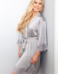 An image of the Grey Moonstone Dorotea Robe being worn by a blonde lady with her hair out. The Robe is tied with a matching belt sash, and drapes flatteringly to her knee. The sleeves are detailed with delicate lace detailing which is very elegant.