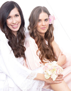 An image of a bride and her brunette bridesmaid, who is wearing the Rose Quartz Dorotea Robe. They are both sitting amongst pink and white flowers. The delicate pink colour of these robes are feminine and subtle.