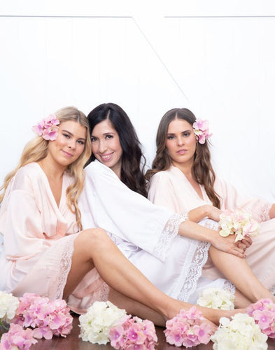 An image of a bride and her two bridesmaids, who are both wearing the Rose Quartz Dorotea Robe. One a brunette and one a blonde, they are both sitting amongst pink and white flowers. The delicate pink colour of these robes are feminine and subtle.