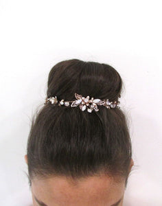 An image of the Elena Bridal Hair Vine with its filagree floral design of clear crystals, pearls and opalescent beads intricately placed on rose gold moveable wiring. The piece is placed in a brunette up-do hairstyle.