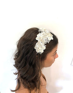 An image from above of the Emily Bridal Headband showing the lace flower design with pearls, crystals and rhinestones on a silver-toned headband. The piece is placed in a brunette flowing curled hairstyle.