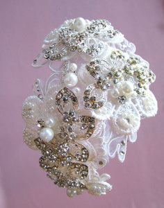 A close up image of the Emily Bridal Headband showing the elegant detailed lace flower design with pearls, crystals and rhinestones on a silver-toned headband. The piece is placed in a brunette flowing curled hairstyle.