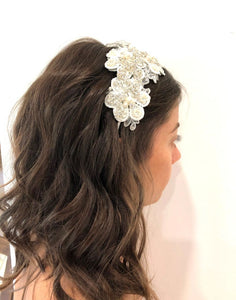 An image of the Emily Bridal Headband showing the lace flower design with pearls, crystals and rhinestones on a silver-toned headband. The piece is placed in a brunette flowing curled hairstyle.