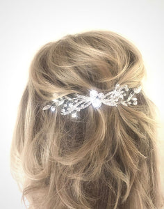 An image of the Faye Bridal Comb showing the shimmering faceted crystal embellishments in a slimline silver-toned design is placed vertically in a blonde half up-do hairstyle.