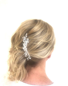 An image of the Faye Bridal Comb showing the shimmering faceted crystal embellishments in a slimline silver-toned design is placed vertically in a blonde side-do hairstyle.