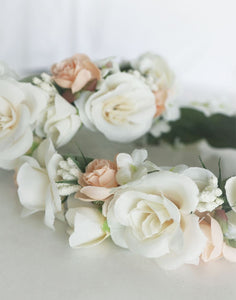 A closeup image of the satin fabric flower girl flower crown. This image shows in detail the mix of ivory and blush coloured satin roses, embellished with delicate gypsophila and snowdrop flowers. Soft green felt leaves which line the headpiece can be seen behind.
