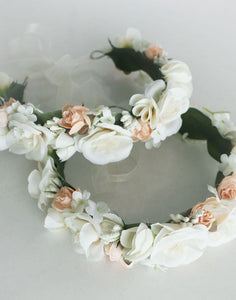 An image of two satin fabric flower girl flower crowns placed on top of one and other. This image shows the mix of ivory and blush coloured satin roses, embellished with delicate gypsophila and snowdrop flowers which are lined with soft green felt leaves and fastened with a soft ribbon tie.