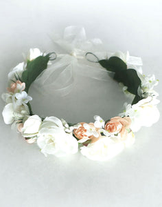 An image of the satin fabric flower girl flower crown. This image shows the mix of ivory and blush coloured satin roses, embellished with delicate gypsophila and snowdrop flowers which are lined with soft green felt leaves and fastened with a soft ribbon tie.
