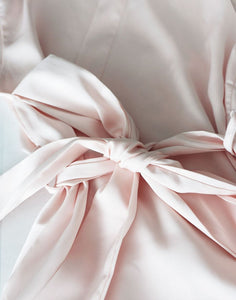 A closeup image of the Rose Quartz coloured belt sash, which matches the robe. It is tied in a lovely bow, and shows the soft drape of the silk satin fabric.
