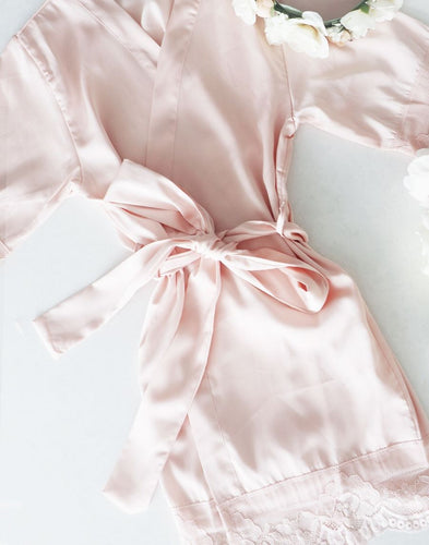 An image of the Dorotea flower girl robe, which is laid flat. The feminine rose quartz colour of the robe with matching belt sash is truely elegant. The lace detail can be seen on the hem.