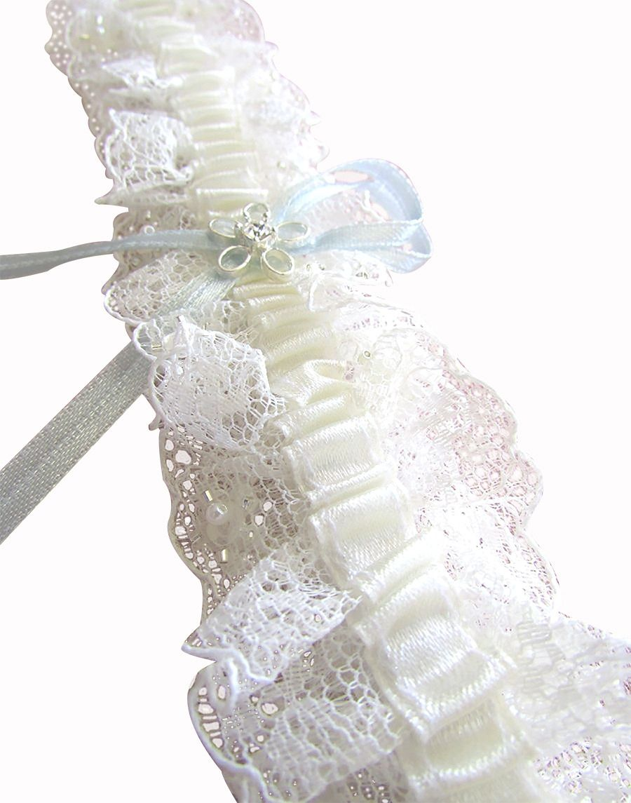 A closeup image showing the delicate, handcrafted classic Gina Bridal Garter. the image shows the crystal, beading and pearl intricate detailing as well as the subtle blue satin ribbon centred on a thicker Ivory ribbon