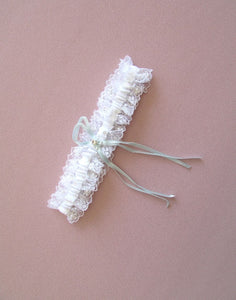A wider angled image showing the complete Gina White Carter. The design is a classic bridal garter design. With lace and a white satin ribbon accentuated with intricate beading, pearls and crystals. The subtle thin blue satin ribbon is entered with a flower shaped crystal.