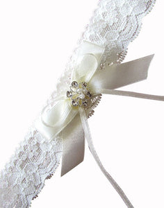 A closeup mage showing the elegant Lace Crystal Garter. The design uses soft high-quality lace, and this image shows the handcrafted detail of crystals and pearls in a flower silver setting, centred in two ivory satin bows.