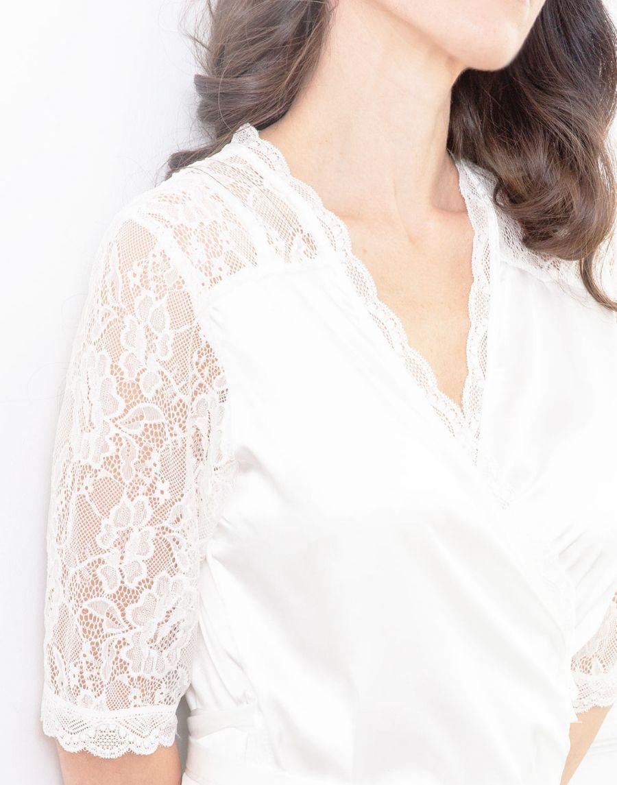 A closeup image of the Luce Silk Lace Robe. This image shows the top section of this robe. The main robe is made from soft, light fabric and the front neckline and sleeves are a delicate floral lace. Detail in this design is so feminine and elegant.