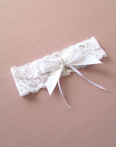 A wider angled image of the lace Maeve white lace bridal garter. The design is a wide flower patterned soft stretch lace which is detailed with handcrafted with white satin ribbon bows with a rhinestone motif.