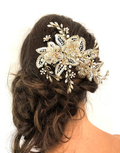 An image of the Maria Bridal Comb Hairpiece showing the glass, Swarovski & pearl detailed Bridal Comb placed in a brunette curled low updo hairstyle.
