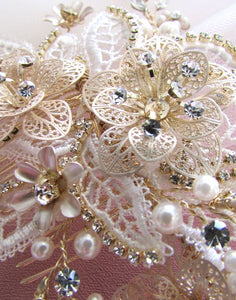 A closeup image of the Maria Bridal Comb Hairpiece showing it's glass, Swarovski & pearl detailing on gold-toned wiring.