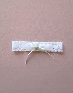 A wider angled image of the Mia Lace Garter. This garter is made from flower patterned soft stretch lace, organza and satin bows, with a clear glass metallic sparkle motif in the centre.