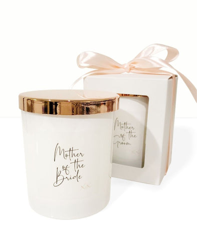 An image of the Mother of the Bride candle. This image shows the beautiful white candle vessel and the rose gold lid. The personalised 'Mother of the Bride' text is in a funky elegant cursive text on the front of the candle. Another candle is displayed in the background, showing the gift packaging of a white box and peach bow that the candle is packed in
