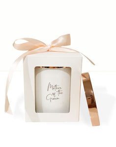 An image of the Mother of the Bride candle. This image shows the beautiful white candle vessel and the polished rose gold lid. The personalised 'Mother of the Bride' text is in a funky elegant cursive text on the front of the candle. The candle is gift packed in a simple white box, with peach bow