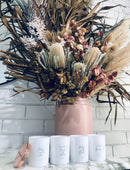 Load image into Gallery viewer, A lifestyle image of the personalised candles. This image shows four beautiful white candle vessels, and the  polished rose gold lid.  The candles are open, and placed on a marble counter, in front of an arrangement of Australian Native flowers. A Polished rose gold candle lid is leaning against the first candle on the left.