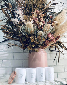 A lifestyle image of the personalised candles. This image shows four beautiful white candle vessels, and the  polished rose gold lid.  The candles are open, and placed on a marble counter, in front of an arrangement of Australian Native flowers. A Polished rose gold candle lid is leaning against the first candle on the left.